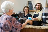 Mid adult waitress with colleague serving coffee to senior woman at counter in cafe