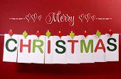 stock photo of pegging  - Merry Christmas greeting message across red and green letter cards hanging from heart shape pegs on a line bunting with text against a festive red background - JPG