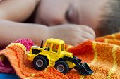 stock photo of power-shovel  - Little bulldozer toy and boy sleeps in background - JPG