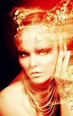 Art project: beautiful woman with golden make-up. Jewelry, make-up. Fashion. Light effects.