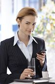 Smiling businesswoman using mobilephone having coffee-break, looking at camera.