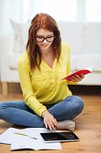 business, education and technology concept - smiling female student in eyeglasses with notebooks and