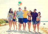 summer, holidays, vacation, happy people concept - group of friends having fun with ball on the beac