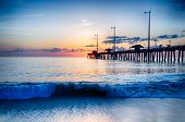 The Rising Sun Peeks Through Clouds And Is Reflected In Waves By The Nags Head Fishing Pier On The O