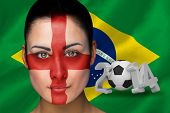Composite image of england football fan in face paint with brasil flag