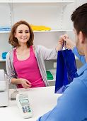 image of over counter  - Happy Female Cahier Handing Over Shopping Bag To Customer - JPG