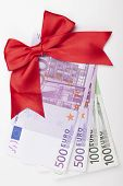 stock photo of payday  - Euro banknotes with red ribbon isolated on white backgroound - JPG