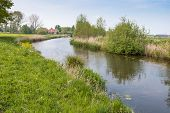 Curved Stream In A Polder Landscape In Springtime