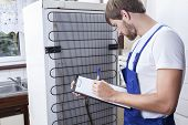 picture of handyman  - Horizontal view of handyman during fridge repair - JPG