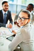 Attractive businesswoman in eyeglasses looking at camera on background of her colleagues