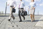 Businesspeople running on bridge
