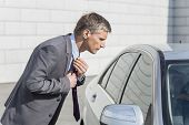 Side view of businessman adjusting tie while looking in car window