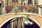 Venice, Italy. A bridge with flowers buquet over a narrow canal among old Venetian architecture. Vintage