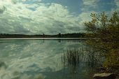 stock photo of puffy  - this image is about beautiful white puffy clouds with blue sky over small lake in autumn .