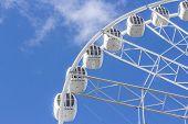Ferris wheel on a background of blue sky
