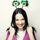 Beautiful young surprised woman with funny green eyes. Studio shot.