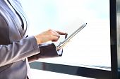 Businesswoman's hand presses on screen digital tablet
