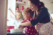 stock photo of casual woman  - Mother with her 5 years old kids cooking holiday pie in the kitchen to Mothers day - JPG