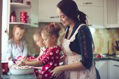 Mother with three kids cooking holiday pie in the kitchen, casual lifestyle photo series in real life interior