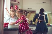 stock photo of three sisters  - Mother with three kids cooking holiday pie in the kitchen - JPG