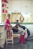 picture of three sisters  - Mother with three kids cooking holiday pie in the kitchen - JPG