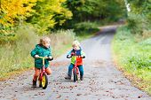foto of four-wheel drive  - Two little children having fun on bikes in autumn forest.