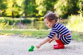 Cute Princess Girl In Red Rain Boots Playing With Rubber Toy Frog