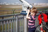 Little Blond Boy Watching Airplanes In Observation Tube On Airport
