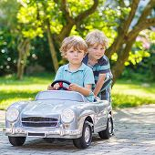 Two Happy Children Playing With Toy Car