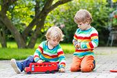 Two Little Friends Playing With Red School Bus