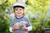 Happy Kid In Skipper Uniform Playing With Toy Ship