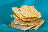 Baked potato crisps with Mediterranean herbs on green background