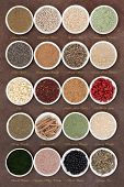 foto of ashwagandha  - Body building powders and super health food in porcelain dishes over natural lokta paper background with titles - JPG