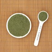 stock photo of oleifera  - Moringa oleifera herb powder ayurvedic alternative medicine and superfood in a white porcelain bowl and measuring spoon over bamboo background - JPG