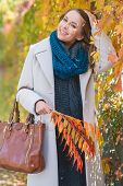 Stylish young woman in a polo neck and coat walking in a park picking decorative autumn leaves and looking at the camera with a lovely smile