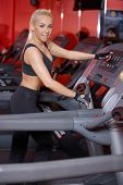 Strong athletic tanned blond woman working out on gym equipment turning to give the camera a happy s