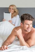 Macro Happy Handsome Couple Partner on Bed While Pretty Partner Holding a Gadget at the Back in Fashion Shoot
