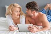 Young White Couple Lying in Bed Arguing Something What They Saw on Tablet.