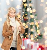 winter holidays, fashion and people concept - smiling young woman in winter clothes over christmas tree lights background