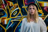 pic of nose piercing  - portrait of a young blonde girl with nose piercing and color graffiti background - JPG