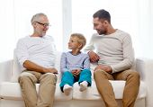 family, happiness, generation and people concept - smiling father, son and grandfather sitting on co