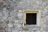 Old Square Window With Bars In A Stone Wall