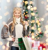 happiness, winter holidays and people concept - smiling young woman in winter clothes with shopping bags over christmas tree background