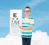vision, health, ophthalmology, childhood and people concept - smiling little boy in eyeglasses with eye chart over blue sky background