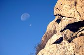 stock photo of wane  - A double waning moon against a blue sky near an outcropping of rocks - JPG