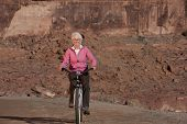 Senior Woman Riding Bike Through The Desert