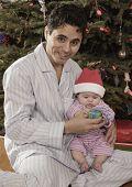 Hispanic father giving Christmas gift to baby