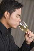 Hispanic man drinking wine