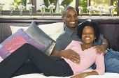 Young African couple smiling on bed