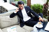 Attractive rich man in suit talking on mobile phone smiling